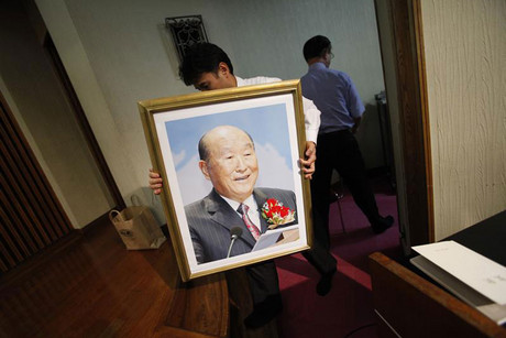 A believer carries a portrait of Sun Myung Moon (Reuters)
