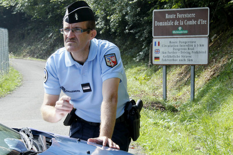 A French gendarme checks notes as he blocks the access road to La Combe d'Ire in Chevaline (Reuters)