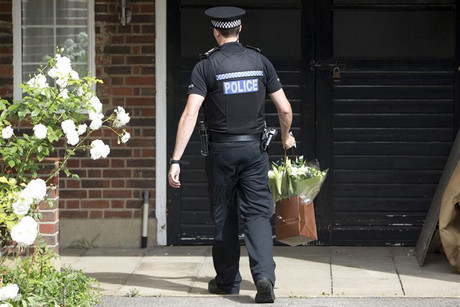 A police officer lays flowers at the home of Saad al-Hilli in Claygate, southern England (Reuters)
