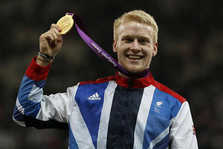Britain's Peacock lifts his gold medal after receiving it for winning the men's 100m T-44 final in the Olympic Stadium at the London 2012 Paralympic Games (Reuters)