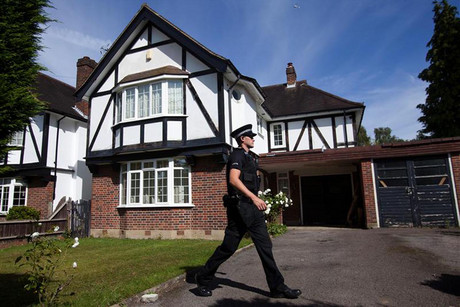 A police officer walks in the grounds of the home of the al-Hilli family  (Reuters)