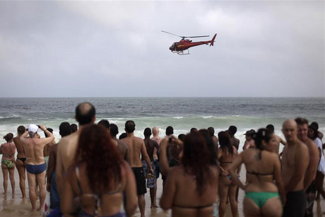 Beachgoers observe as firefighters search for a helicopter which crashed in the sea (Reuters)