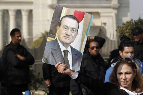 A supporter of Egypt's deposed president Mubarak holds up his picture outside the Maadi Armed Forces hospital (Reuters)