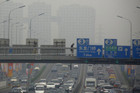 A pedestrian walks across a bridge above a main road on a day with high air pollution in Beijing (Reuters)