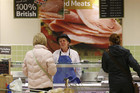 A worker serves customers in the meat department of a Tesco supermarket (Reuters file)