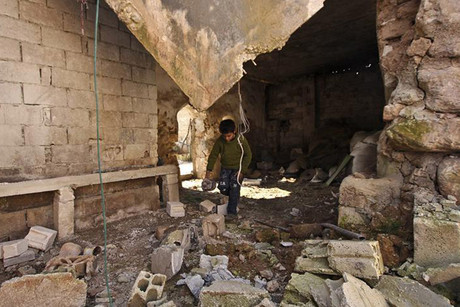 A boy inspects house which rebels say was damaged by government forces near Idlib (Reuters)