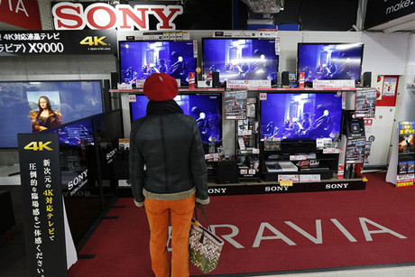 A woman looks at Sony's TV sets at an electronic shop in Tokyo (Reuters)