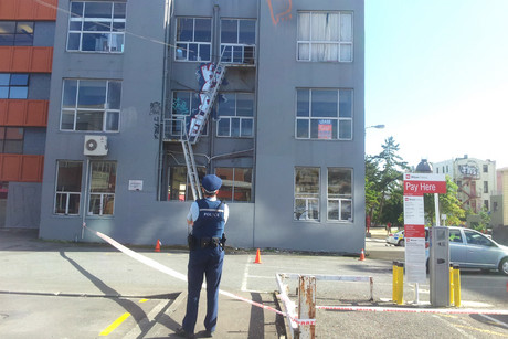 A police officer looks at the fire escape which the woman is believed to have fallen from (photo: Lloyd Burr/3 News)