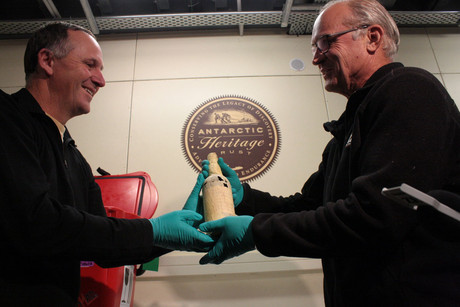 Prime Minister John Key, left, hands back a bottle of century-old whisky from Ernest Shackleton's British Antarctic Expedition to the Antarctic Heritage Trust's Rob Fenwick after the whisky was sample for recreation (AAP)