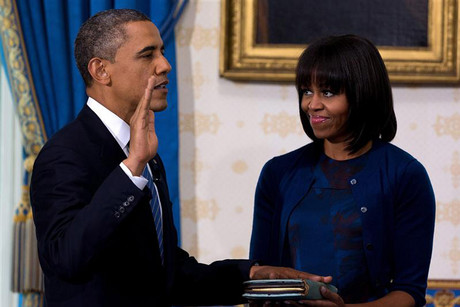 US President Barack Obama takes the oath of office as first lady Michelle Obama holds a bible during the official swearing-in ceremony (Reuters)