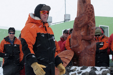 John Key stands in front of a new pou whenua, or carved post, which was unveiled during a short ceremony at New Zealand's Scott Base in Antarctica (AAP)