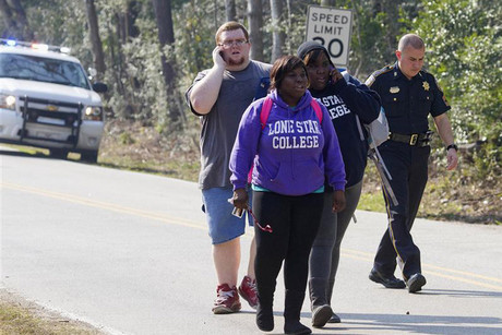 A sheriff's deputy escorts students from the Lone Star College campus in Houston (Reuters)