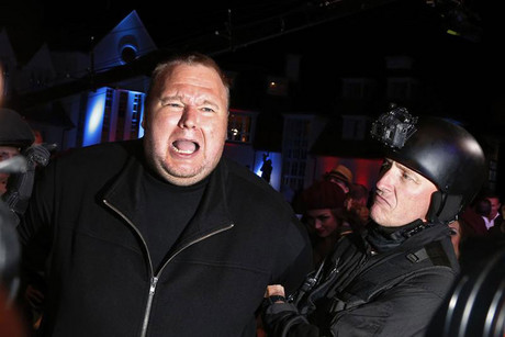 "An actor in police costume mock-arrests Kim Dotcom as he launches his new website ""Mega"" in Auckland (Reuters)"