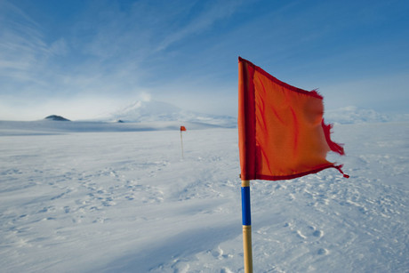 A red flag blows in the wind on the McMurdo sound ice shelf with Mt Erebus and Ross Island in the background