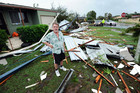 A man stands infornt of a house damaged by mini-tornadoes that tore through the costal township of Bargara, near Bundaberg in Queensland (AAP)