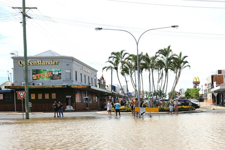 Residents look as the Burnett river which floods the town of Bundaberg, QLD (AAP)