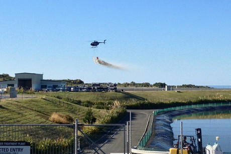 The helicopter sprays lime slurry on one of the ponds (photo: Richard Torres / 3 News)