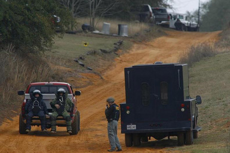 Bomb squad members are driven to the scene of the hostage standoff in Alabama (Reuters)