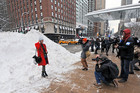 A woman poses for photographers in front of a large snow mound before attend Mercedes-Benz Fall Fashion Week in New York (AAP)