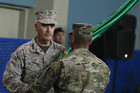 US General Joseph Dunford hands an ISAF flag to an army personnel during a change-of-command ceremony in Kabul (Reuters)