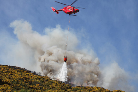A helicopter douses the flames which are heading towards houses (photo: Samantha Ives/ 3 News)