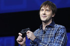 PlayStation 4's lead system architect Mark Cerny holds a gaming control device during the unveiling of the PlayStation 4 launch event in New York (Reuters)