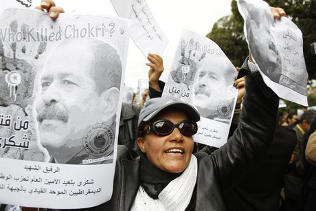 A woman chants slogans and holds pictures of assassinated leftist politician Chokri Belaid during a demonstration against the Islamist Ennahda movement in Tunis (Reuters)