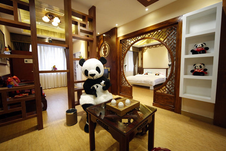 An employee dress in a panda costume in one of the hotel's rooms (Reuters)