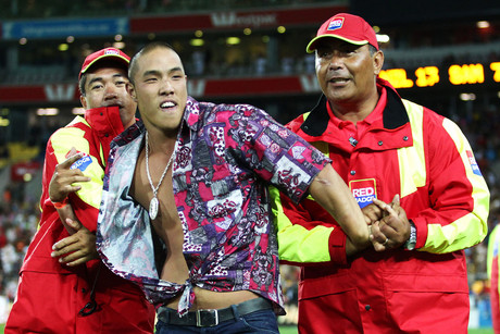 A pitch invader is held by Red Badge security during the Sevens (Photosport)