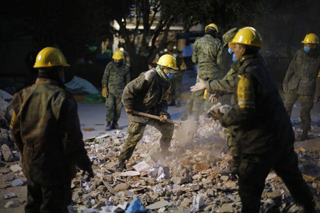 Military personnel remove debris from the site of an explosion at the headquarters of state-owned oil giant Pemex (Reuters)