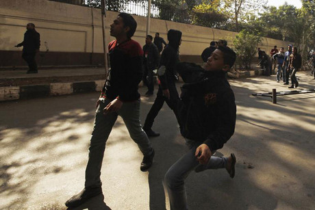 Protesters opposing Egyptian President Mohamed Mursi throw stones at riot police during the funeral of activists Mohamed al-Gendy and Amr Saad in Cairo (Reuters)