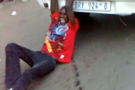 A still image from video of the incident showing Mido Macia handcuffed to the back of a van