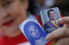 A woman holds pictures of Jesus Christ and Hugo Chavez outside the military hospital where he is being treated (Reuters file)