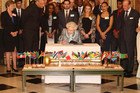 Britain's Queen Elizabeth signs the Commonwealth Charter at a reception at Marlborough House in central London (Reuters)
