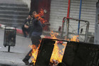 A Palestinian throws stones at Israeli security forces during clashes in the West Bank city of Hebron, March 8 (Reuters)