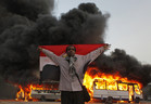 An anti-Mursi protester stands with the national flag after protesters burn Muslim Brotherhood buses during clashes near the Muslim Brotherhood's national headquarters in Cairo's Moqattam district (Reuters)