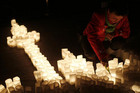 A woman ignites candles during Earth Hour in Frankfurt (Reuters)