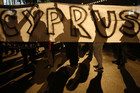 "Anti-Troika protesters hold a ""Hands off Cyprus"" banner during a demonstration outside the EU offices (Reuters)"