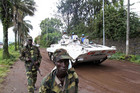 A United Nations peacekeepers' armoured vehicle drives past Congolese Revolution Army rebels patrolling a street in Goma (Reuters)