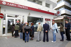 Depositors wait for the opening of a branch of Laiki Bank in Nicosia (Reuters)