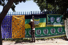 A man adjusts the ANC flag next to banners with images of Nelson Mandela (Reuters)