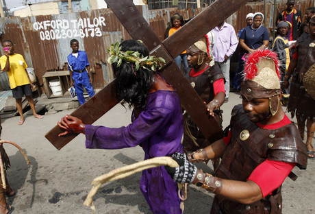A man playing the role of Jesus Christ is escorted by guards during a ritual procession re-enacting the death of Christ in Lagos while in Jos more than 50 have been killed after officials pleaded for peace over the easter weekend (Reuters)