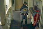 Police CCTV  footage shows a man dressed as Batman and a burglary suspect stand in a police station in Bradford, northern England (Reuters)