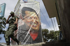 A poster of Hugo Chavez close to the military hospital in Caracas where he is being treated (AAP)
