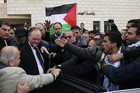 British Consul-General Sir Vincent Fean (2nd L) is escorted into his car as Palestinian students protest against his visit to Ramallah (Reuters)