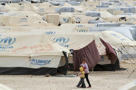 Syrian refugee children walk along tents at the Al Zaatri refugee camp in the Jordanian city of Mafraq (Reuters)