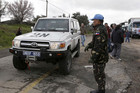 A Filipino United Nations peacekeeper stands next to a U.N. vehicle before it crosses from Israel into Syria (Reuters)