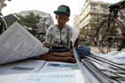 A boy selling newspapers folds them before selling them in Yangon (Reuters)