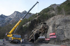 A crane hoists the bus which crashed and burned on the road from l'Alpe d'Huez in the French Alps (Reuters)