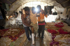 A Bangladeshi worker is helped into a tent after the shooting (Reuters)